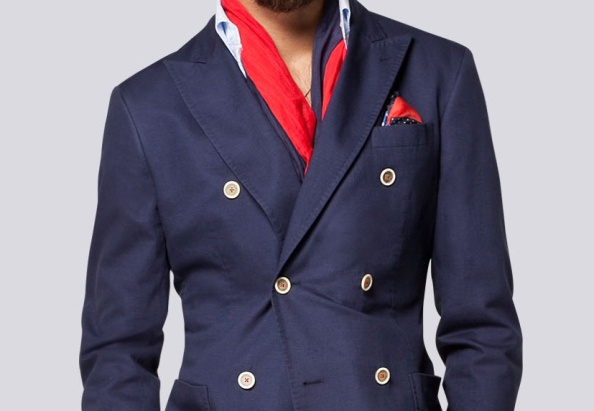 The red thread detailing on the cream horn buttons bring an otherwise typical navy double breasted blazer to life. Pay attention to the pick stitching on the lapels and the patch pockets.