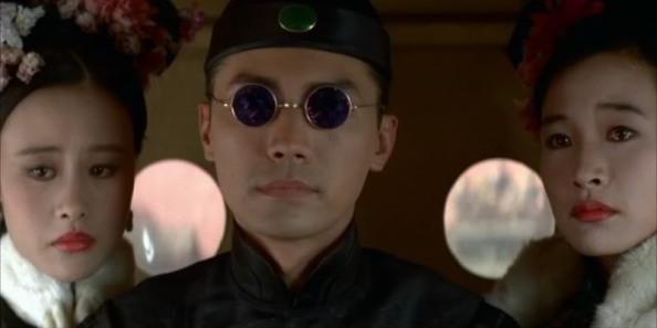 John Lone portrays Pu Yi in Bertolucci's The Last Emperor. He's wearing round sunglasses.