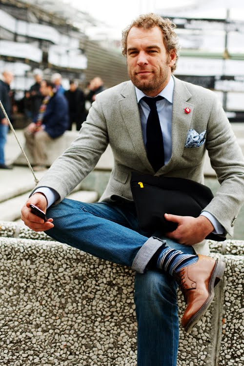 "Socks, laced up oxfords, neck tie properly done and blazer buttoned. You know what makes this a ""business casual"" look? he turned up the cuffs of his denim jeans. Subtle but effective."